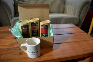 A gift in a brown box and a mug from West Coast Cocoa